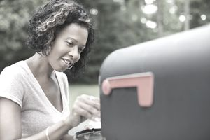 African American woman taking mail from mailbox
