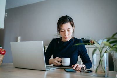 Young woman works on laptop and cellphone while drinking coffee