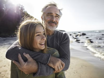 Father hugs adult daughter on sunny day at the beach