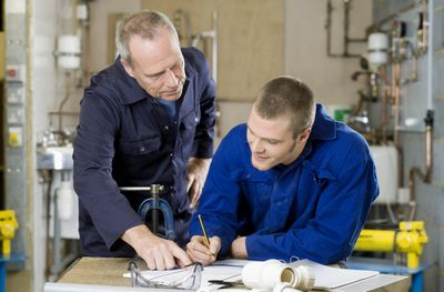 Personnel in plumbers' uniforms review documents
