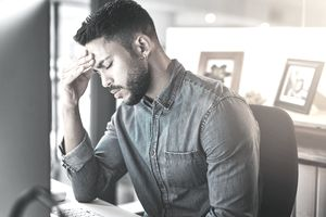 Young adult in jean shirt with hand on his head, stressed out in front of computer