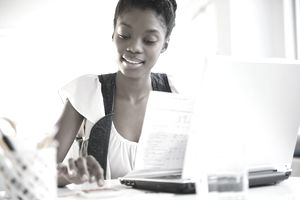 Woman using calculator and looking at paperwork while sitting in front of a laptop