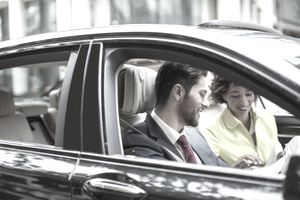 Couple reviewing paperwork in the front seat of a car