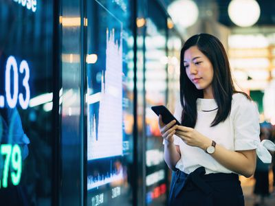 Woman looking at stock quotes on monitors and her phone