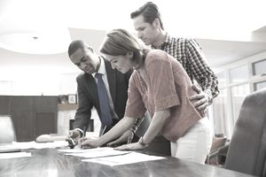 Man and woman in office signing documents with a businessman