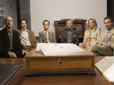 Group of men and women seated in front of desk with copies of a will