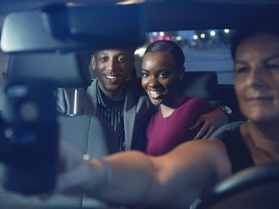 Couple in taxi booked with ride share app