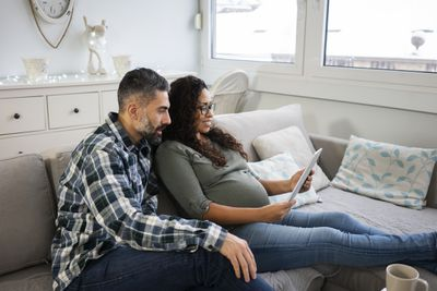 A man with a beard and a pregnant woman sit on a couch looking over their budget on a tablet