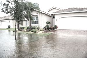 Flooding from a hurricane as water creeps up on a home covering the sidewalk and part of the driveway