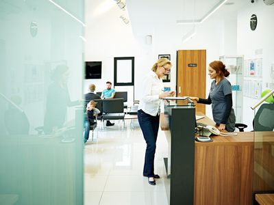 Dental hygienist helps female patient with paperwork at reception desk