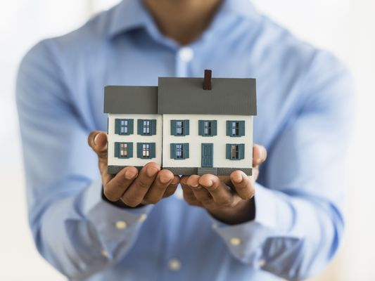 Man in blue button up shirt holding miniature house carefully in his hands