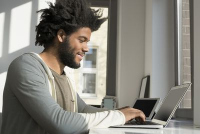 Person working at home, smiling at laptop