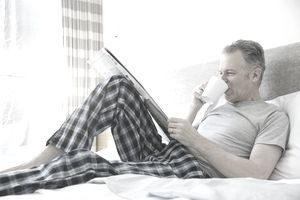 Man drinking coffee in bed