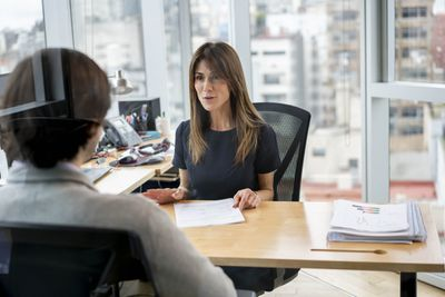 Professional talking to colleague in her office while holding paperwork