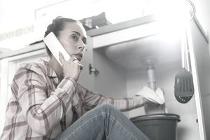 Woman making a phone call while trying to stop a leaking kitchen sink pipe