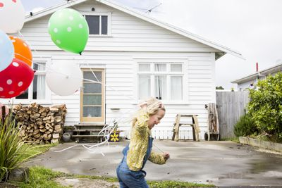 A child holds balloons while running in front of a house