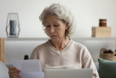 Focused serious old mature woman looking through paper documents.
