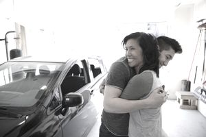 Son Hugs His Mother in a Home Garage, Holding Keys and Next to a Car