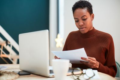 Woman working on her finances at home, filling up tax forms