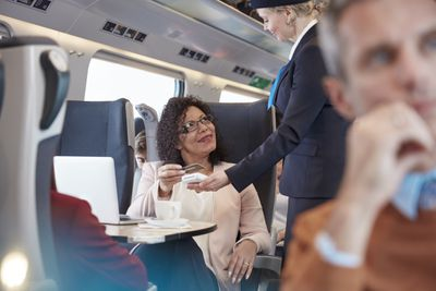 Woman with credit card using contactless payment, paying attendant on passenger train.