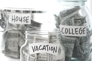 Various jars filled with money and labeled for goals of college, house, and vacation
