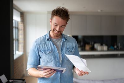 Happy man at home checking the mail.