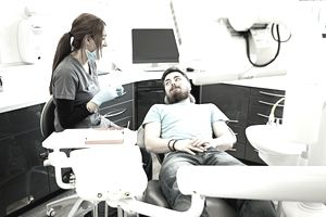 Female dentist with young male patient Indoor shot of female dentist with young male patient in the dentist chair