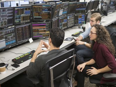 Group of young people analyzing stock market data at trading desk