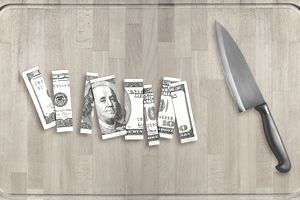 A $100 bill chopped into pieces on a cutting board with a sharp knife laying nearby