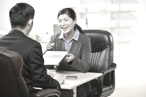 Asian businesswoman pointing to paperwork