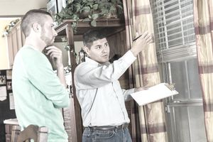 Home inspector gesturing toward a window and explaining damage and repairs to homeowner