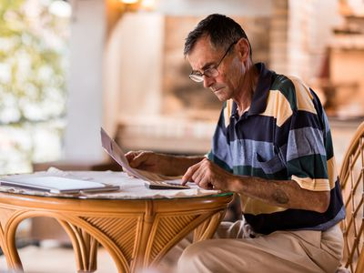 Senior man seriously evaluating paperwork at a small, round table at home