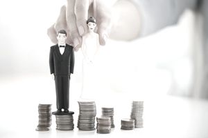 hand placing a wedding cake bride and groom on top of stacks of coins