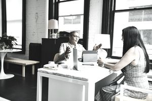 two women talking to each other across a desk about financial matters
