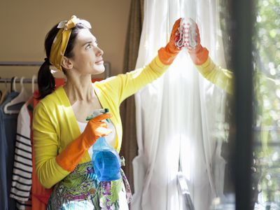 Woman cleaning windows in home