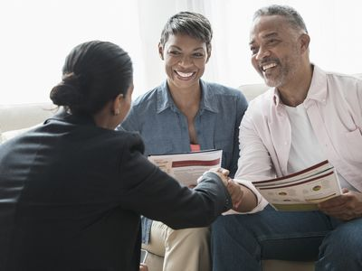 Black couple talking to businesswoman in their home
