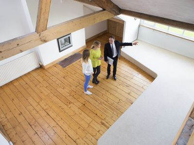 Real estate agent showing empty home to buyers