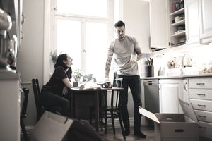Smiling woman looking at man holding glass in kitchen.