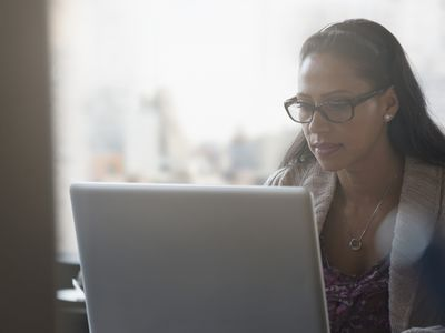 Focused person wearing glasses looking at a computer screen