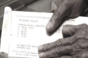 Hands of an elderly man holding his pension booklet open to details of his payment