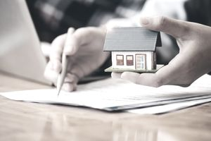 Close up of a model house with a hand putting signing a short sale contract