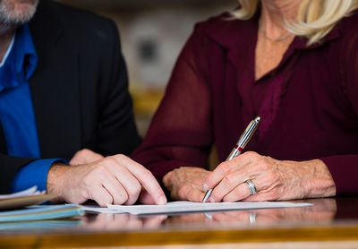 an older woman signing a document