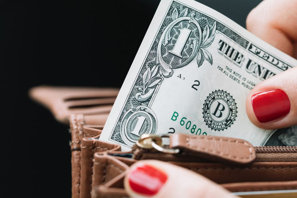 Woman removing dollar bill from wallet