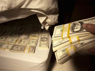 Person places bundles of cash beneth a mattress to save for retirement
