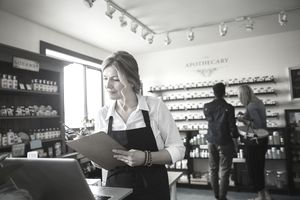 Apothecary shop owner checking inventory at laptop