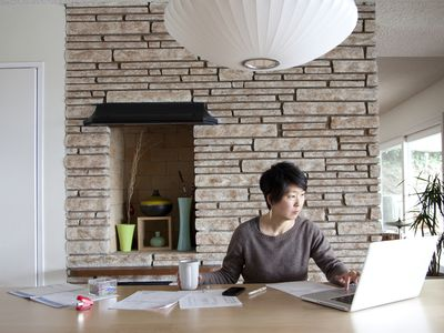 Woman working on financial paperwork on laptop in her home at laptop with coffee