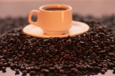 A cup of coffee on a pile of coffee beans