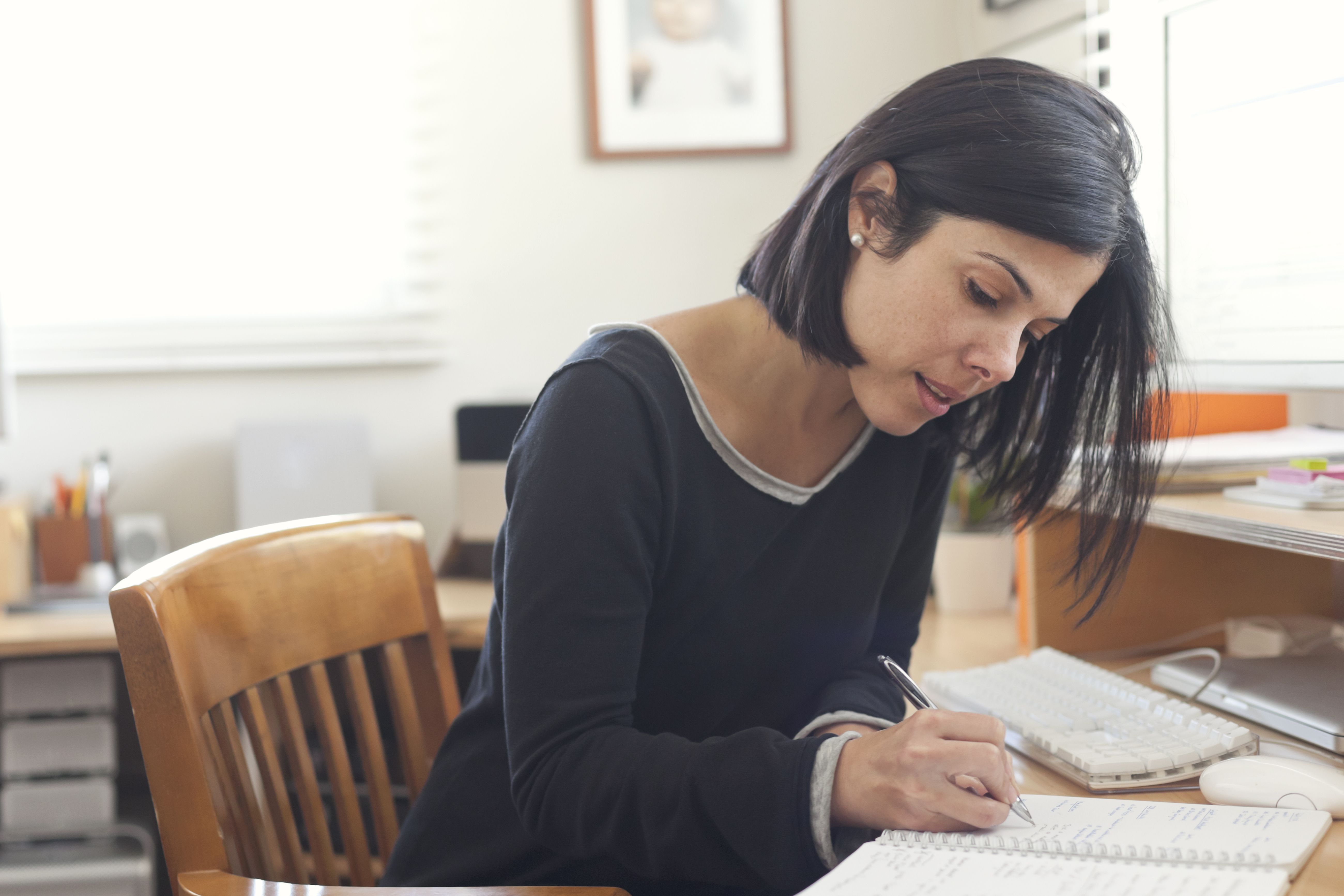 Woman sitting at her desk making a list in her notebook.
