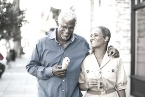 Retired couple walking down sidewalk with ice cream