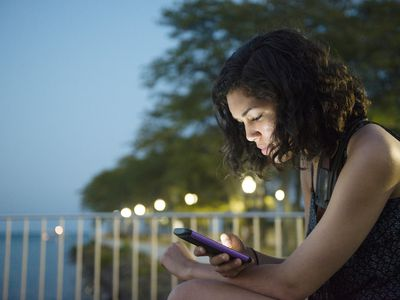 woman with curly hair sits outside at dusk, looking down at her phone thoughtfully